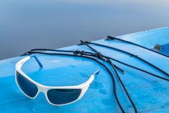 Sport sunglasses on stand up paddleboard Stock Photo