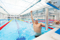 Sport swimmer winning. Man swimming cheering celebrating victory success smiling happy in pool wearing swim goggles and Stock Photo