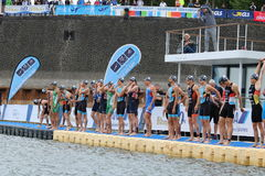 Sport swimming triathlon. A large group of male swimmers lined up on a pontoon ready to race in a triathlon in the Media Hafen at Dusseldorf, Germany Royalty Free Stock Photos