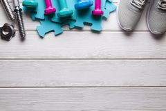 Sport symbols and accessories - dumbbell and sneakers on wooden. Sport symbols and accessories - dumbbell and sneakers on white wooden background royalty free stock photos