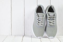Sport symbols - gray sneakers on wooden background. Sport symbols - gray sneakers on wooden wall background stock photos