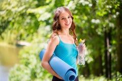 Sport szczęśliwa kobieta z joga matą outdoors obraz stock