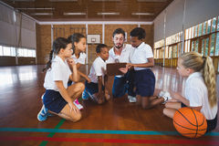 Sport teacher and school kids discussing on clipboard in basketball court. At school gym Royalty Free Stock Image
