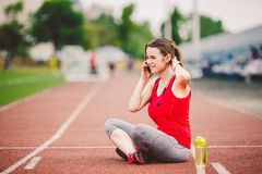Sport and technology. A beautiful young Caucasian woman with ponytail sitting resting after workout during run at stadium, a red t Stock Photos
