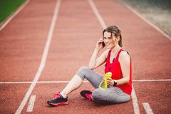 Sport and technology. A beautiful young Caucasian woman with ponytail sitting resting after workout during run at stadium, a red t Royalty Free Stock Photos