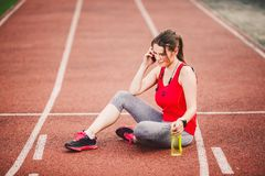 Sport and technology. A beautiful young Caucasian woman with ponytail sitting resting after workout during run at stadium, a red t Stock Photography