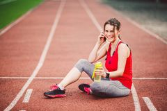 Sport and technology. A beautiful young Caucasian woman with ponytail sitting resting after workout during run at stadium, a red t Stock Image