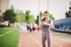 Sport and technology. beautiful young whiteskinned woman with ponytail at running stadium in front of workout uses a sporty smart Stock Photography