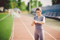Sport and technology. beautiful young whiteskinned woman with ponytail at running stadium in front of workout uses a sporty smart Royalty Free Stock Photo