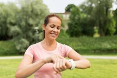 Woman with smart watch or fitness tracker in park. Sport and technology concept - smiling woman with smart watch or fitness tracker in park stock photos