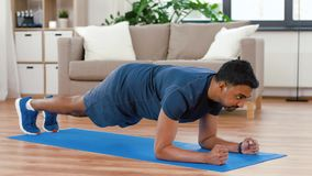 Man with fitness tracker doing plank at home