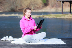 Sport teenage girl using tablet touchpad on pier Royalty Free Stock Photography