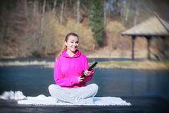Sport teenage girl using tablet touchpad on pier Royalty Free Stock Image