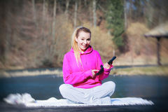 Sport teenage girl using tablet touchpad on pier Stock Photos