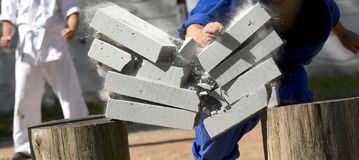 Sport time. Karate man breaking bricks outside Stock Photos