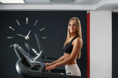 Sport time. Beautiful girl exercising on treadmill Royalty Free Stock Photos