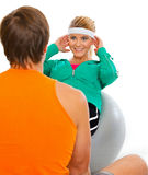 Sport trainer helping girl making abdominal crunch. Personal sport trainer helping healthy girl making abdominal crunch on fitness ball Royalty Free Stock Photos