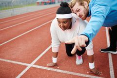 Ready to achieve goal. Sport trainer pointing out goal for young overweight female at low start before running Stock Image
