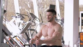Sport training, strong bodybuilder guy sitting doing muscle building workout on traction simulator for hands while. Sport training, strong bodybuilder guy with stock footage