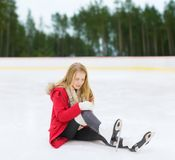 Young woman with knee injury on skating rink. Sport, trauma and winter concept - young woman with knee injury suffering from pain on skating rink royalty free stock image