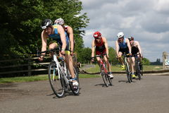 Sport triathlon cycling. A group of male triathletes during the cycling leg of a triathlon at Dorney Lake, England Royalty Free Stock Photography
