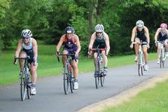 Sport triathlon cycling. Veteran female triathletes in cycling during a triathlon at Dorney Lake, England Royalty Free Stock Photos