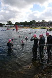Sport triathlon swimming. A group of male triathletes entering the water for a triathlon at Dorney Lake, England Royalty Free Stock Photos