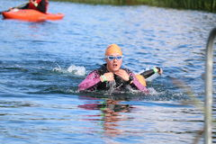 Sport triathlon swimming. A head on view of a female triathlete exiting the swim leg during a triathlon at Dorney Lake, England Stock Images