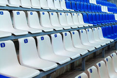 Sport tribune with empty chairs. Blue and white empty seats at the sports stadium Stock Photos