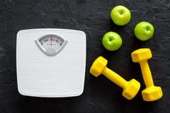 Sport und Diät für verlierendes Gewicht Badezimmerwaage, Apfel und Dummkopf auf Draufsicht des schwarzen Hintergrundes Stockbild