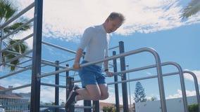 Sport und draußen ausbilden Junger Mann Training in Sportsground und im Handeln-Zug Ups auf Stangen stock video footage