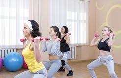 Sport-und Eignungs-Konzepte Fünf Berufssportlerinnen, die Stamm-verbiegende Übungen mit Barbells haben Lizenzfreies Stockfoto