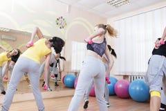 Sport-und Eignungs-Konzepte Fünf Berufssportlerinnen, die Stamm-verbiegende Übungen mit Barbells haben Stockfoto