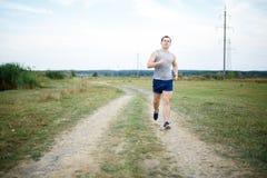 Sport- und Eignungsläufermann, der für Marathonlauf draußen ausbilden tut lizenzfreie stockfotos