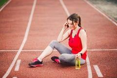 Sport und Technologie Eine schöne junge kaukasische Frau mit dem sitzenden Stillstehen des Pferdeschwanzes nachdem Training währe Stockfotografie