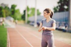 Sport und Technologie verwendet schöne Junge whiteskinned Frau mit Pferdeschwanz an laufendem Stadion vor Training ein sportliche Stockfoto