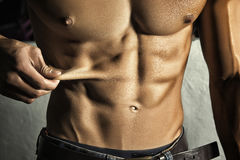 Sport. Unrecognizable man showing his perfect abs with no fat Royalty Free Stock Images