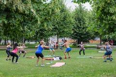Sport utomhus En grupp människor som gör övningar i, parkerar royaltyfria foton