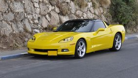 Sport-véhicule jaune sur la route de montagne Photographie stock