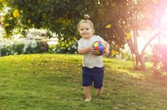 Happy cute baby boy playing with ball on green grass. Sport and vacation. Happy cute baby boy, small, little child with long blond hair, ponytail, barefoot royalty free stock photo