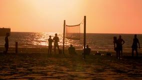 Sport Voetsalvo Jongeren die footvolley, strandvoetbal op de zonsondergang spelen stock footage
