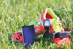Sport watch, chest strap of a heart rate monitor, smartphone with headphone and sneakers. Royalty Free Stock Images