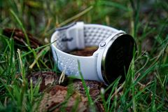 Sport watch for running white color on the ground in the grass. Fitness watch for tracking daily activity and strength training. Sport watch for running white royalty free stock photography