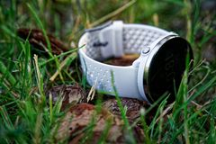 Sport watch for running white color on the ground in the grass. Fitness watch for tracking daily activity and strength training. Sport watch for running white stock photos