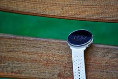 Sport watch for running white color on wooden bench. Fitness watch for tracking daily activity and power training. Sport watch for running white color on wooden stock photography