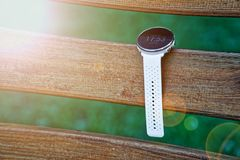 Sport watch for running white color on wooden bench. Fitness watch for tracking daily activity and power training. Sport watch for running white color on wooden royalty free stock image