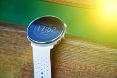 Sport watch for running white color on wooden bench. Fitness watch for tracking daily activity and power training. Sport watch for running white color on wooden stock photo