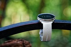 Sport watch for running white color on wooden bench. Fitness watch for tracking daily activity and power training. Sport watch for running white color on wooden royalty free stock photo