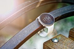Sport watch for running white color on wooden bench. Fitness watch for tracking daily activity and power training. Sport watch for running white color on wooden royalty free stock photography