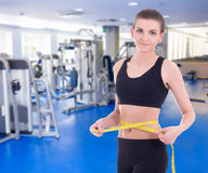 Sport and weight loss concept - beautiful slim sporty woman meas. Uring her waistline with measure tape in modern gym Royalty Free Stock Image
